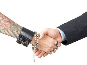 businessman shaking hands with tattooed woman 95363320