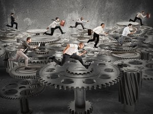 business people running on an endless loop of gears