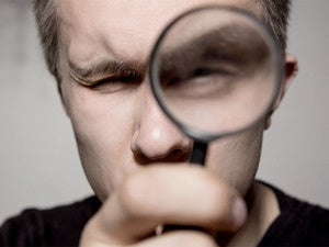 closeup of man holding magnifying glass in front of face