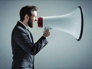 Man standing in profile holding megaphone