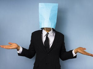 man in dark suit standing with blue paper bag on head
