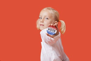 girl with pigtails against orange background holding out vote election pin