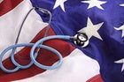 medical stethoscope sitting on top of US flag