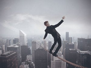 Young executive man balancing on tight rope over city buildings