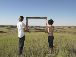 two millennials standing in field holding picture frame against blue sky