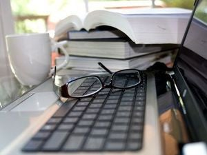 computer keyboard atop which a pair of reading glasses 725x482