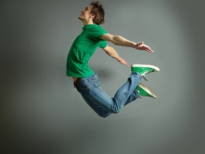 Man in green shirt jumping up in the air
