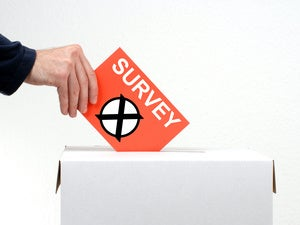 A mans hand and arm are seen depositing a survey into a sealed ballot box
